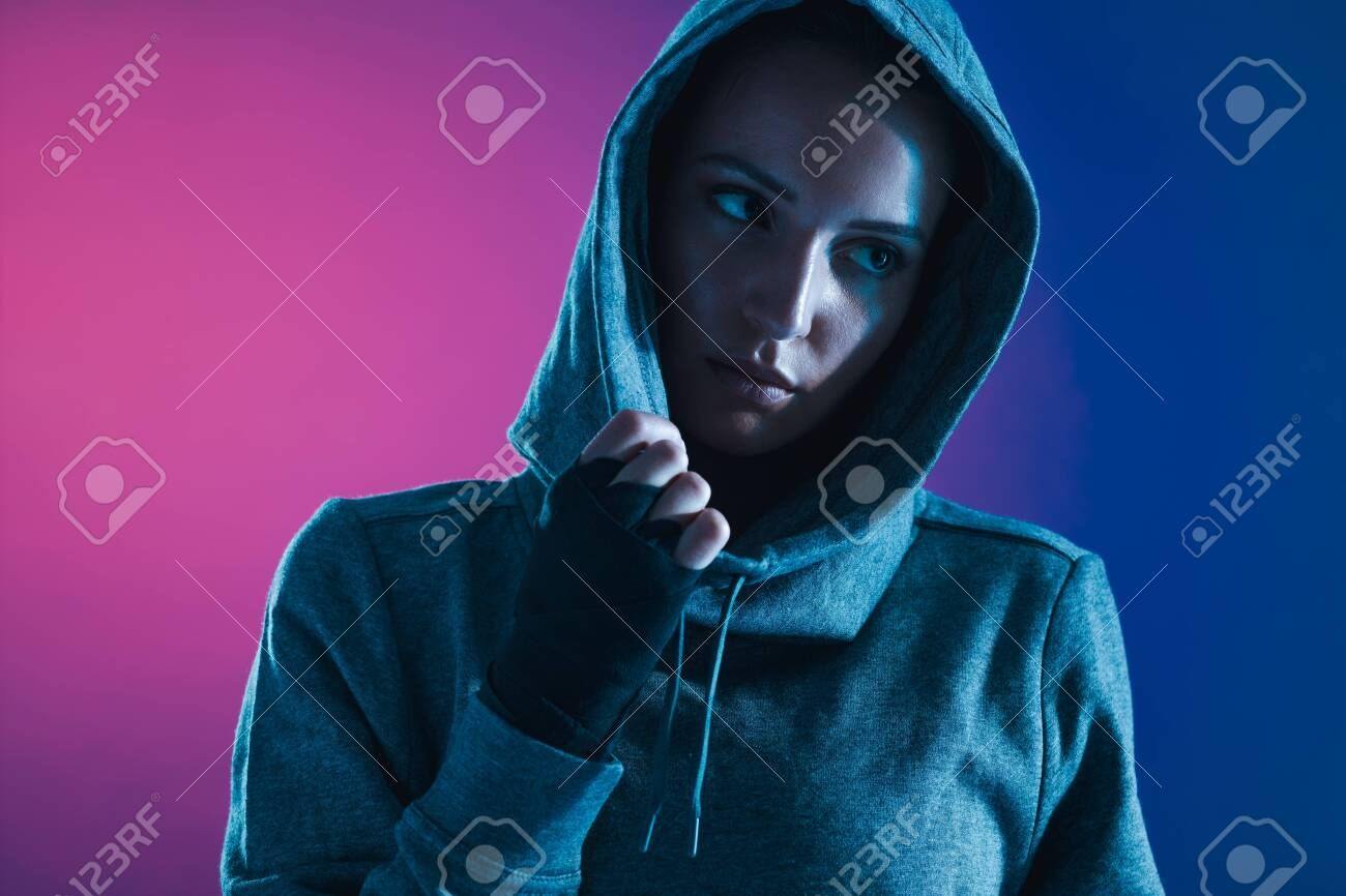 Sportswoman in hooded shirt looking away. Fitness woman looking away against colored background. Sto...