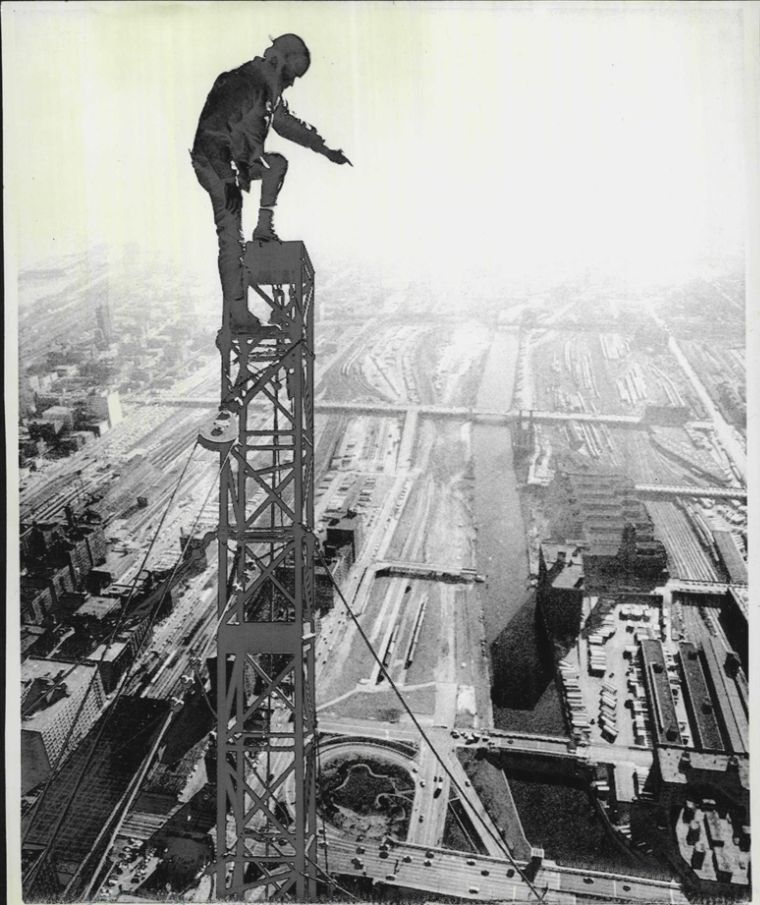 A Construction Worker Stands Atop The Attenna Of The Sears