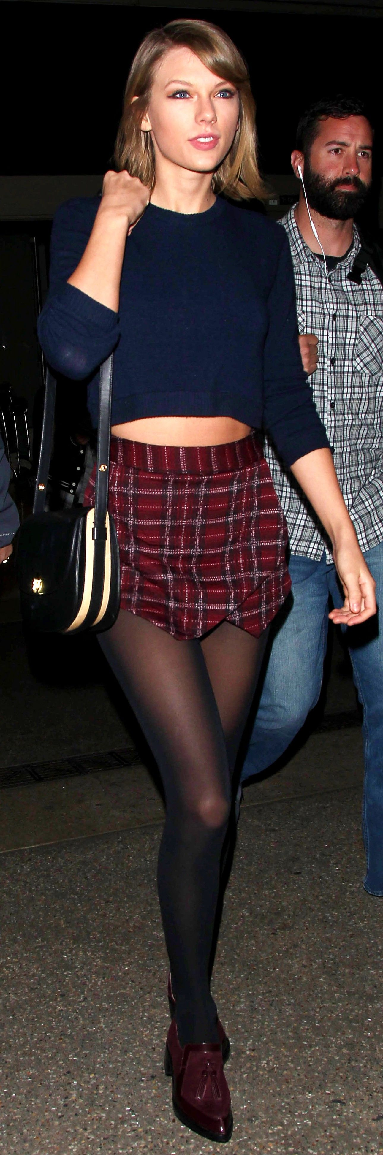 Taylor Swift ; Arriving at Lax Airport in Los Angeles ; December 2015 ; Brandy Melville sweater, Aqua skort, Zimmermann loafers, Zimmermann bag & Wolford tights
