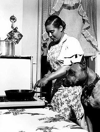 Billie Holiday cooking a steak for her beloved boxer Mister in her Harlem apartment in 1949.