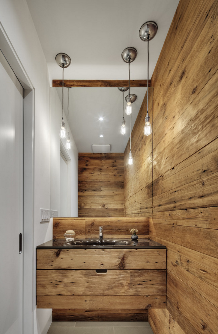 Clean look with industrial pendant lighting, rustic wood wrapping around the wall. Great idea with drawers underneath vanity. The mirror is amazing, it allows the illusion of space.  By Blender Architecture.