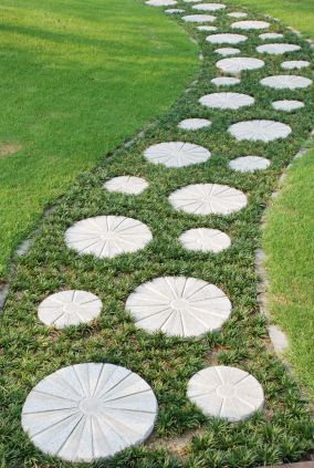 Round Cement Stepping Stones In Groundcover Running Through Grass