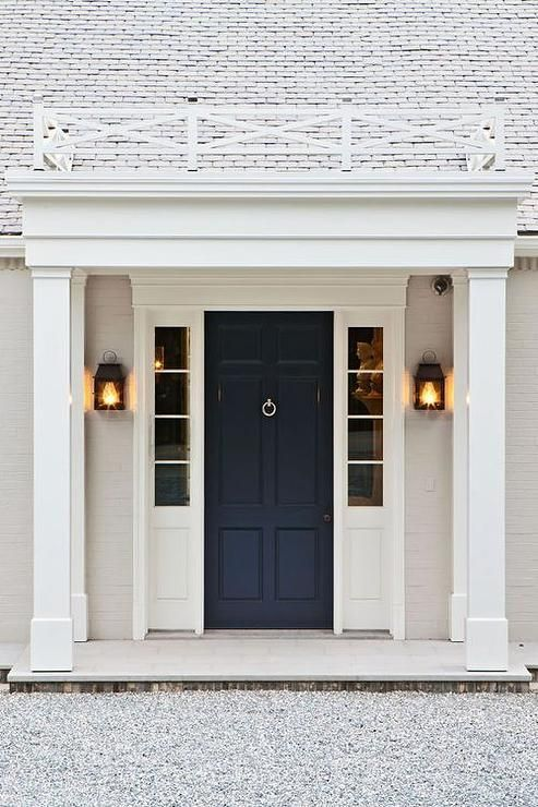 Merveilleux Beautiful Home Exterior Boasts A Navy Front Door Flanked By Sidelights  Illuminated By Carriage Lantern Wall Sconces.