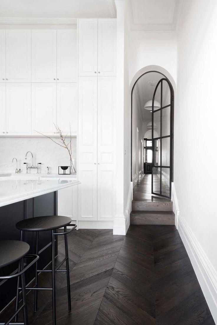 Photo of White kitchen with black arched metal door.