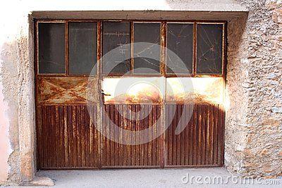 Old Completely Rusty Metal Garage Door With Broken Gl Windows And Rusted Handle