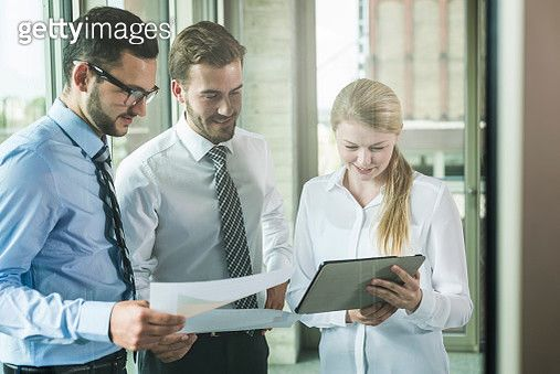 Three young businesspeople looking at documents and digital tablet - gettyimageskorea