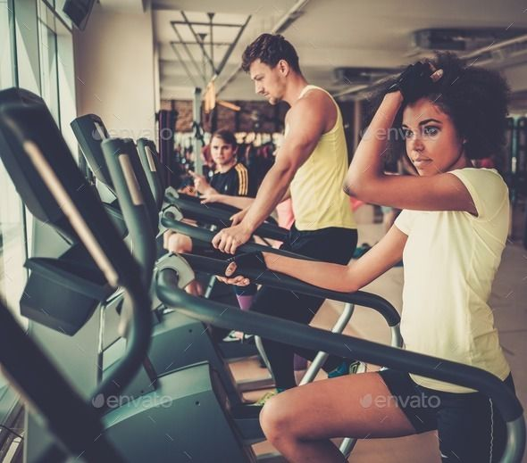 People exercising on a cardio training machines in a gym by Nejron. People exercising on a cardio training machines in a gym #AD #cardio, #exercising, #People, #training