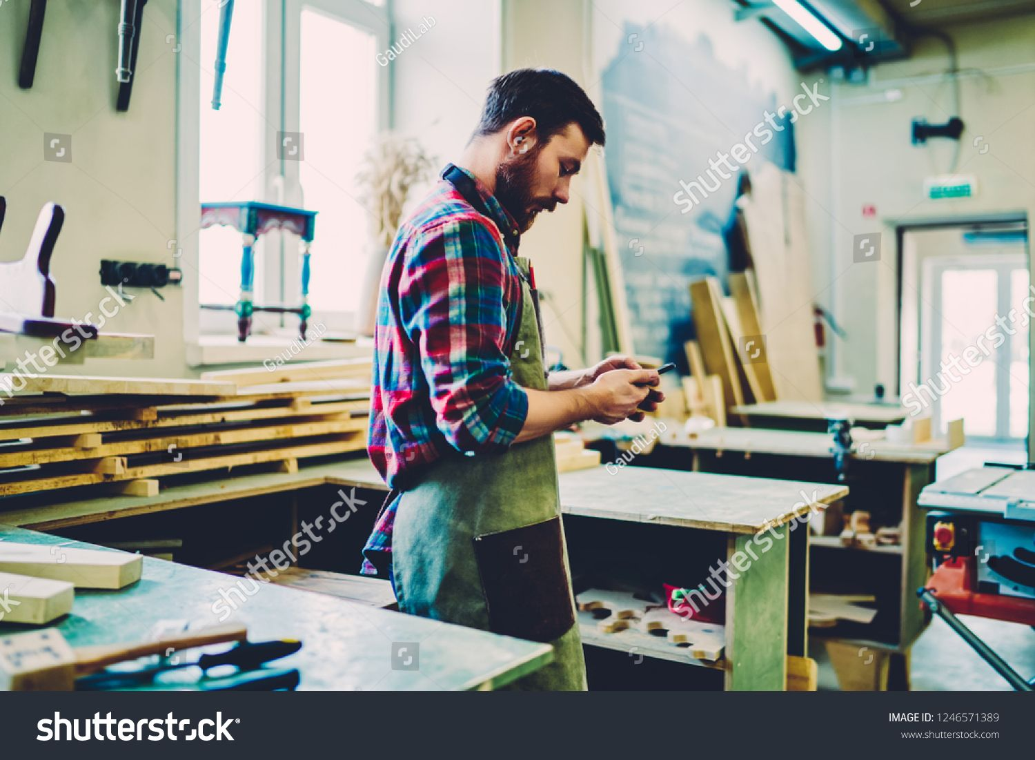Serious Craftsman In Apron Checking Message With Orders On