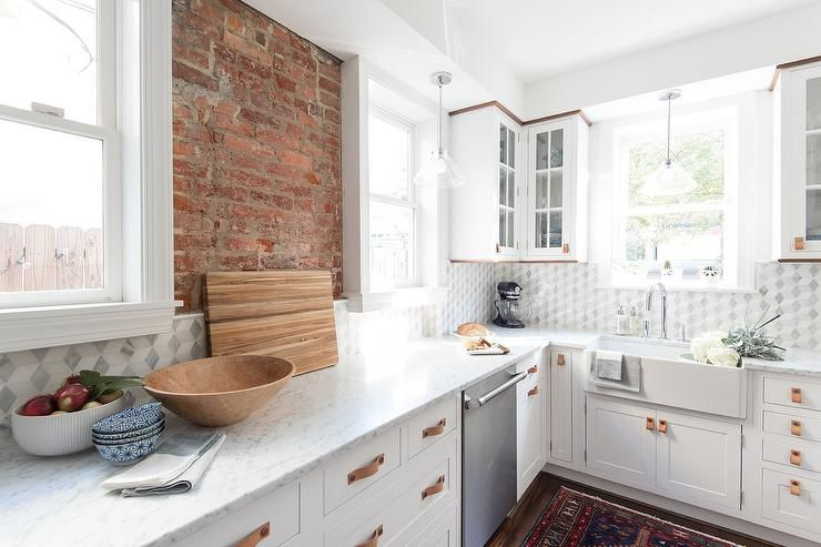 Well Appointed White Kitchen Boasts An Exposed Brick Wall Flanked By Window Lit By Glass Kitchen Backsplash Tile Designs Brick Kitchen Kitchen Tiles Backsplash