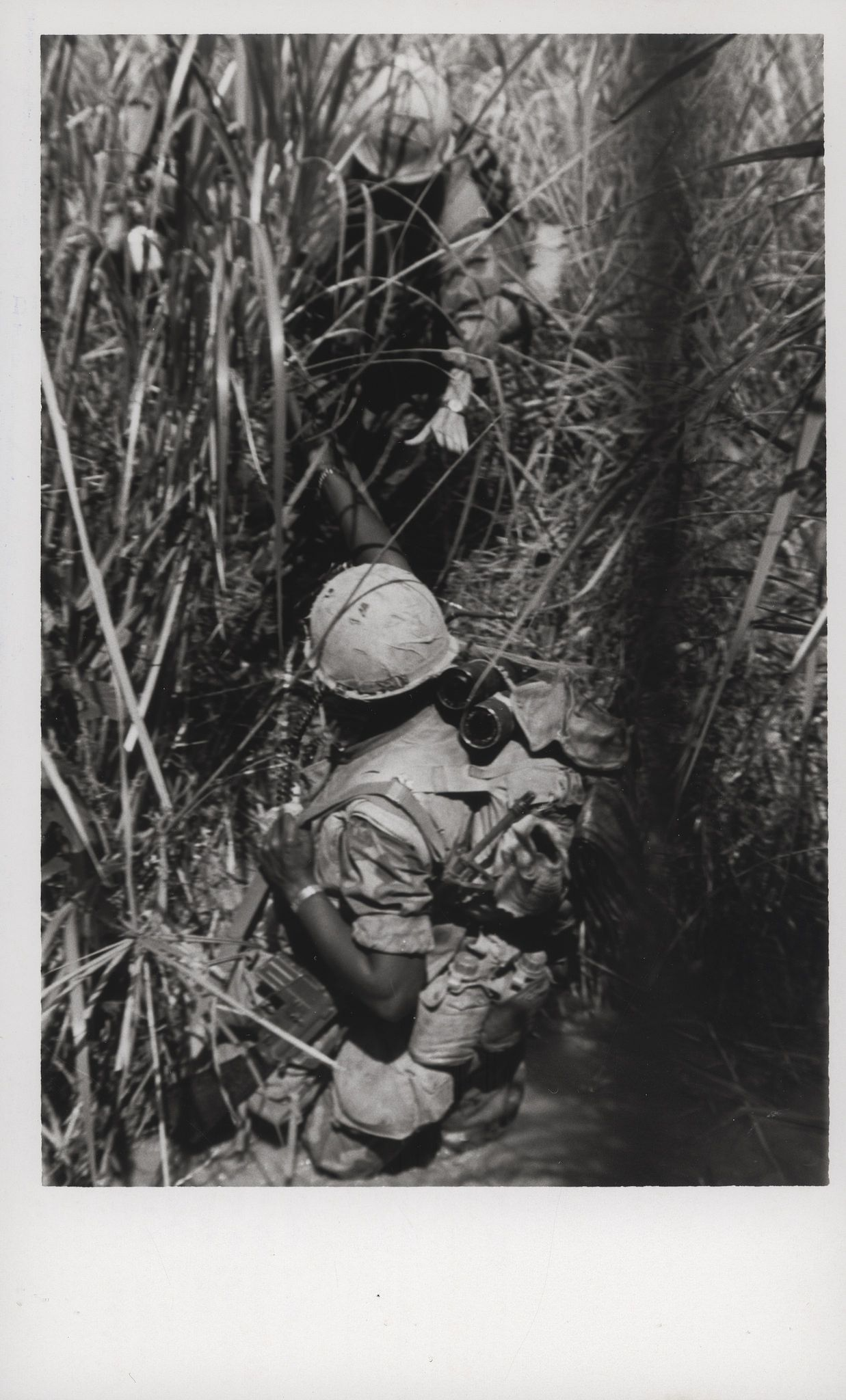 """Marine Lends a Helping Hand, 1969 """"Lending a Hand: An outstretched hand from a Marine buddy helps lift this Leatherneck from a deep stream south of the Demilitarized Zone. The 9th Marine Regiment Leathernecks were participating in Operation Dawson River, west of Khe Sanh in the northernmost province of South Vietnam (official USMC photo by Lance Corporal Don Barr)."""" From the Jonathan Abel Collection (COLL/3611), Marine Corps Archives & Special Collections. OFFICIAL USMC PHOTOGRAPH"""