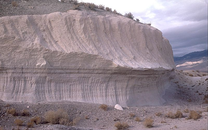 Two layers of the Bishop Tuff: lower layer was from ash fall, upper layer was from the main pyroclastic flow. This is a welded tuff that formed approx. 767,000 yrs ago, as a rhyolitic pyroclastic flow during the eruption that created the Long Valley Caldera. The tuff caps a volcanic plateau in the northern Owens Valley. The tableland formation is E of US Route 395, NW of Bishop and SE of Crowley Lake & Mammoth Lakes. Another part of the flow is S of Mono Lake, & surrounding the Mono-Inyo…