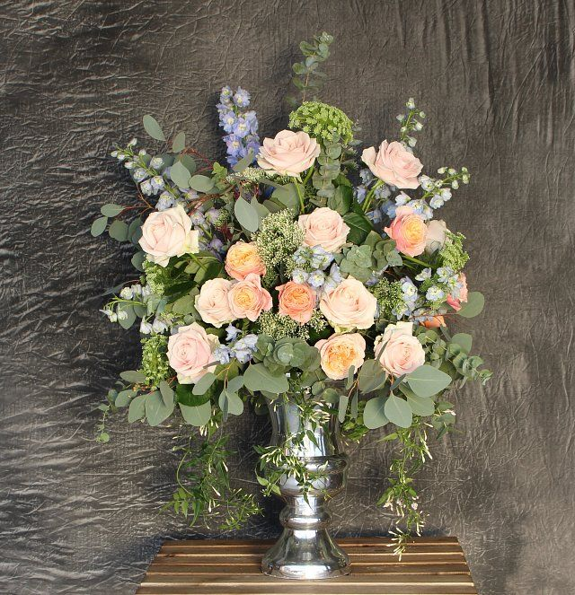Peach tones for this rose filled urn with trailing jasmine