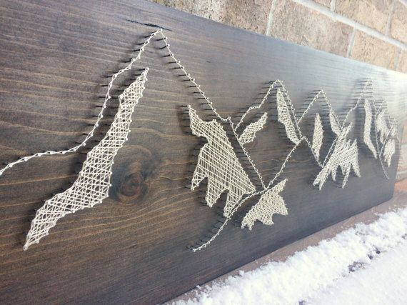 Large string art piece of a landscape mountain view on a dark walnut stained wood board. Extra metallic thread added to some of the ice caps to give it more sparkle in the light alongside the reflecting silver nails. Very unique piece to add to your decor, over a mantle or master bedroom. Protected with cardboard and wrapped in packing paper this ships out well. A peaceful scene for any home. #stainedwood