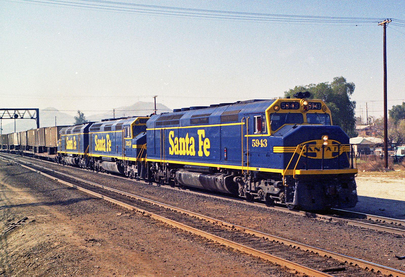 https://flic.kr/p/cP7m8s | Better Blue Than Yellow Bonnet | Santa Fe's eastbound 198 train, the Super C, is about to hammer the diamonds at Colton, CA on Sunday, Feb. 27, 1972. Repainted FP45 5943, leads an F45 and another repainted FP45 in this view shot on Ektacolor film.
