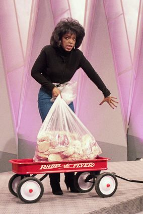 1988 -After losing 67 pounds, Oprah wheels out a wagon loaded with exactly that much fat.