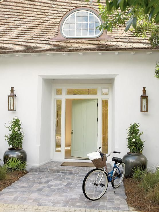 White Beach House Boasts A Pale Green Front Door Accented With Transom Windows And Sidelights Illuminated By Carriage Wall Lanterns