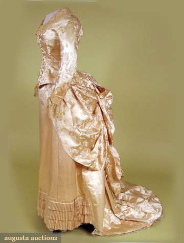 """SHELL PINK SILK RECEPTION GOWN, 1880s1-piece trained gown, bodice attached at pink satin skirt back, bodice & bustled overskirt pale silk brocaded w/ tulips, front self covered buttons, neckline & flounced cuffs trimmed w/ fine ecru lace, skirt w/ 3 rows pleated self trim at hem, pale pink cotton twill lining, skirt lined w/ stiffened buckram, train lace trimmed pleated hem protector, Sh-Sh 14.5"""", B 34"""", W 22"""", Slv L 23"""", Skirt L 39""""-59"""", (1 missing button, light stains on train back)…"""