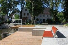 Die zentrale Grünfläche vor dem Rathaus mit Weiher wurde im Rahmen der Maßnahme renoviert und durch verschiedene Aufenthaltsbereiche ergänzt. Die Platzflächen ermöglichen eine Nutzung für Boulespiel, Veranstaltungen oder Markt.
