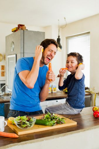Stock Photo : Father and young son singing into carrot microphones