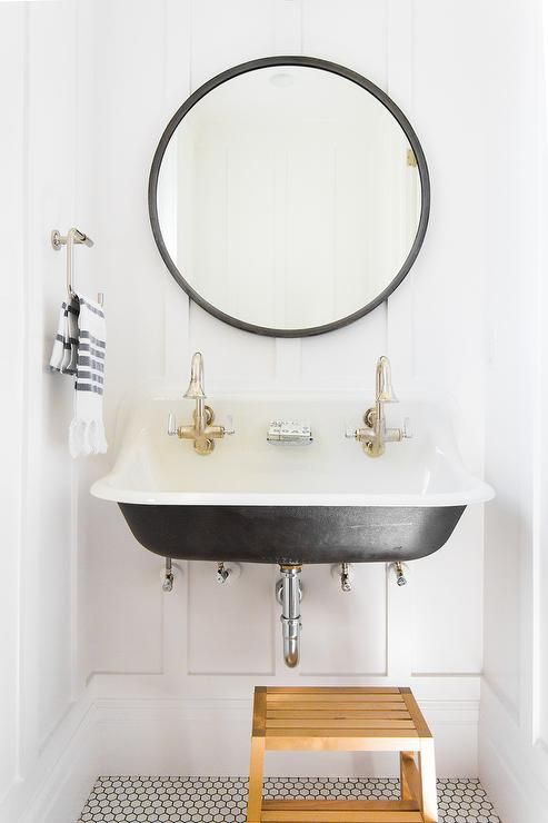 Black and white kids' bathroom boasts a teak step stool placed on white hive tiles with black grout in front of a Kohler Brockway Sink fitted with two nickel faucets positioned beneath a round black vanity mirror mounted to a white board and batten covered wall.