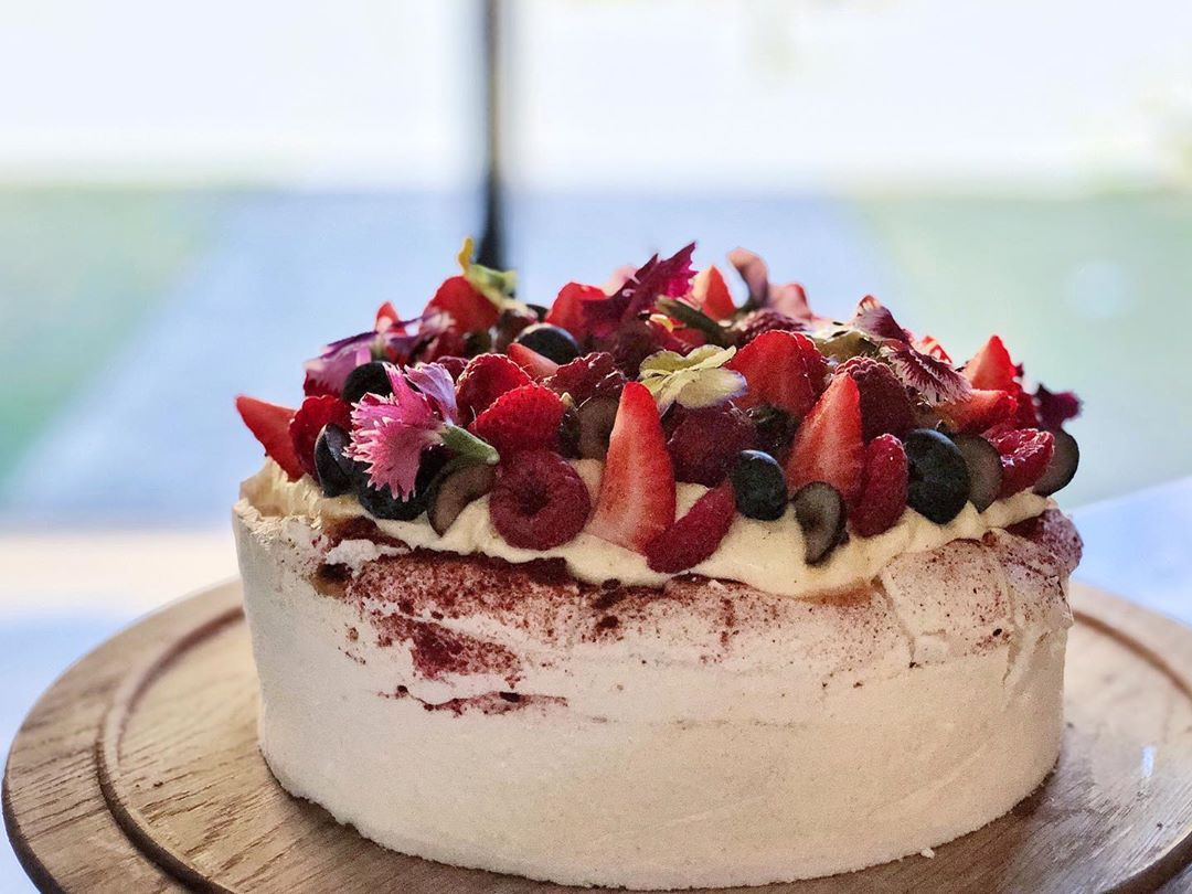 Pavlova made with freeze dried strawberry powder and fresh berries in season on top. Made today for a special occasion