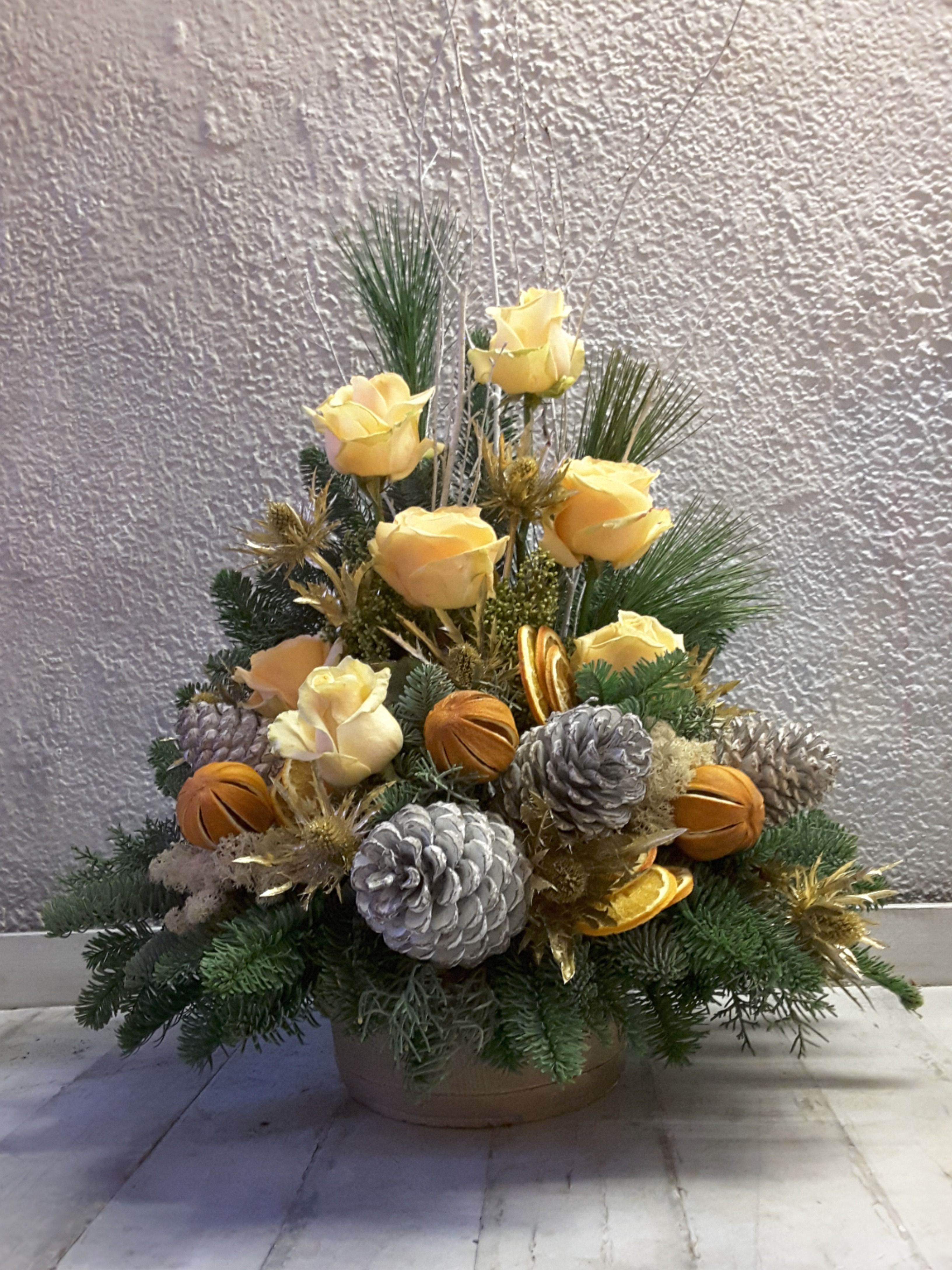 A winter themed arrangement, in a container, of cream