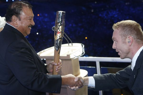 Olympian Chris Hoy (right) hands the queen's baton over to Commonwealth Games federation president Prince Imran.