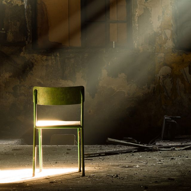 A Lone Green Chair In A Dark Dirty Room, A Ray Of Sunlight Shines .