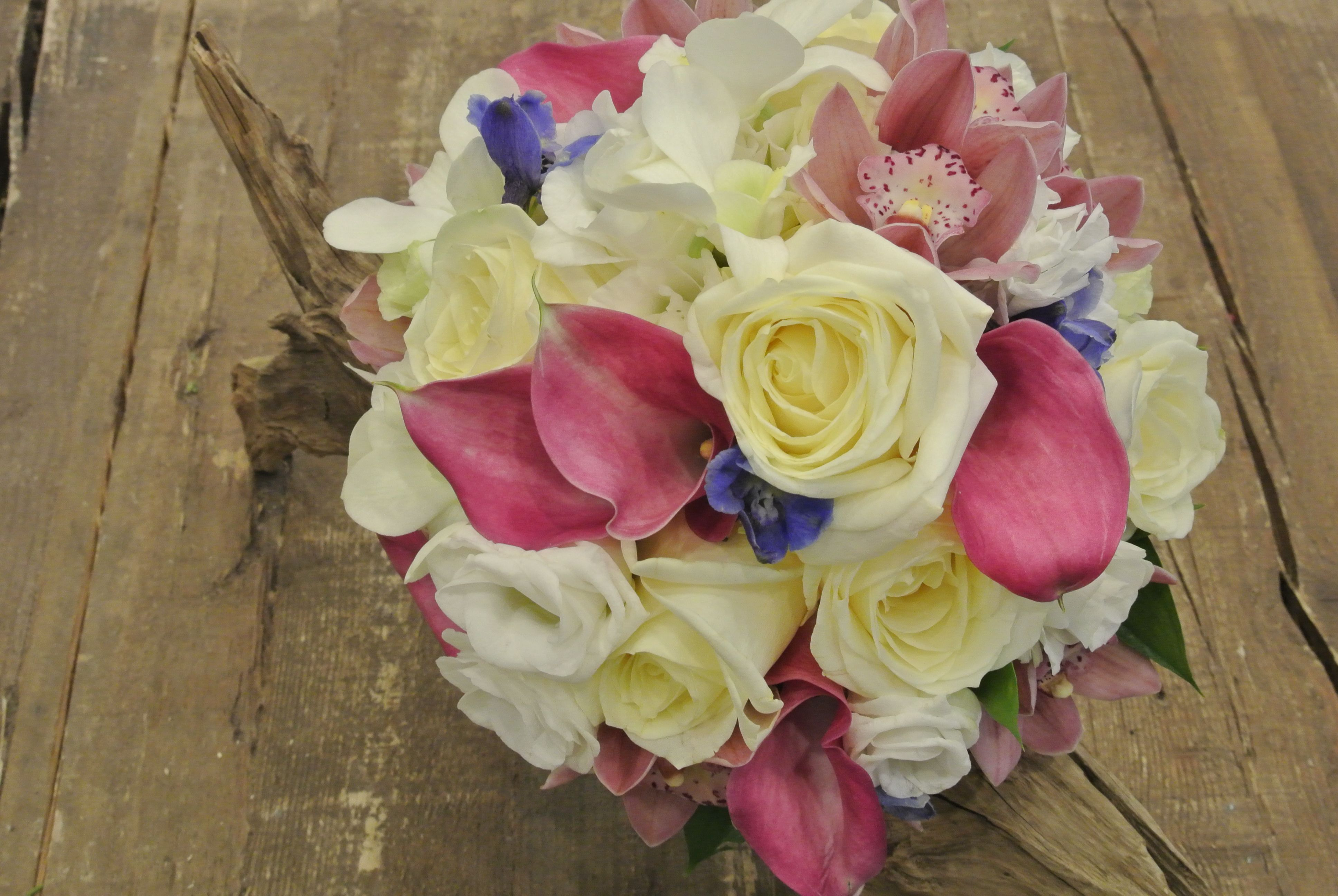 Bridal bouquet with ivory roses pink calla lilies lisianthus bridal bouquet with ivory roses pink calla lilies lisianthus cymbidium orchids and blue delphinium designed by forget me not flowers izmirmasajfo