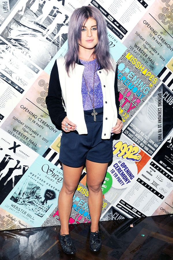black and white varsity jacket, shimmery purple top, high-waisted shorts, and glittery oxfords