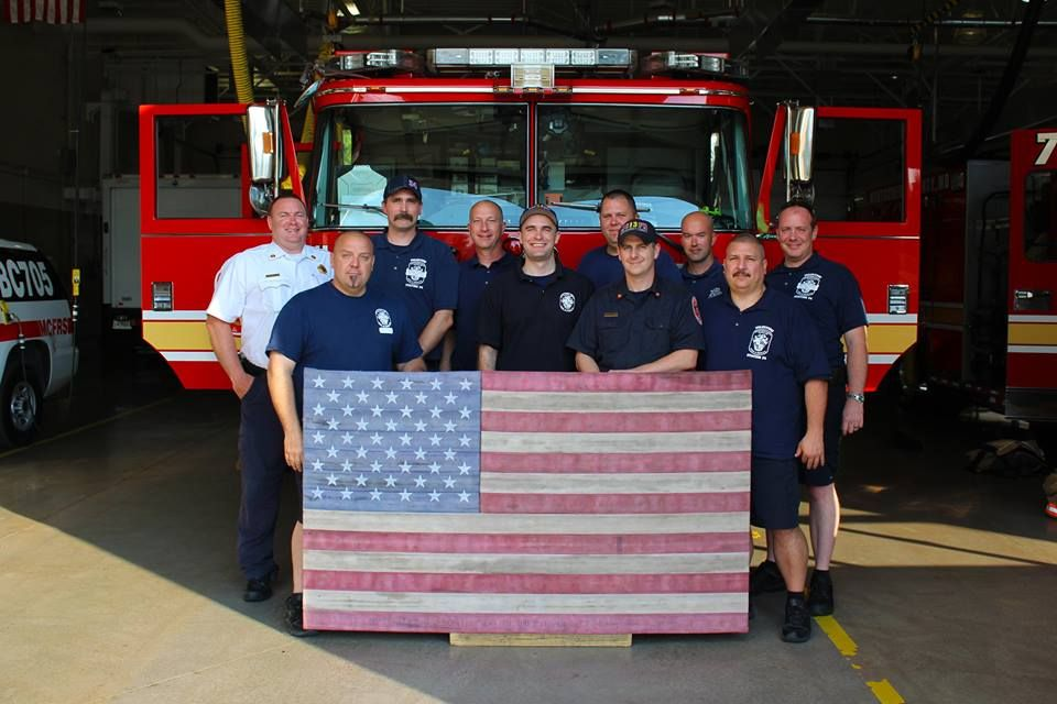 fire station 34 crew with US flag made out of recycled fire hose