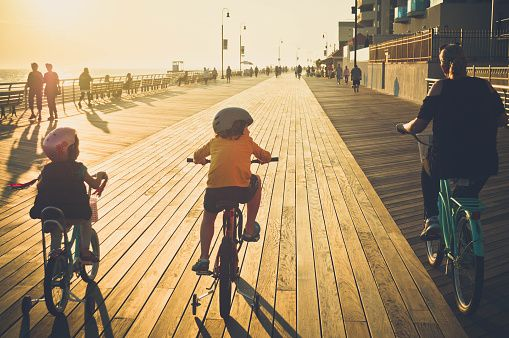 family-riding-bikes-on-the-boardwalk-at-the-beach-picture-id615860620 (509×338)