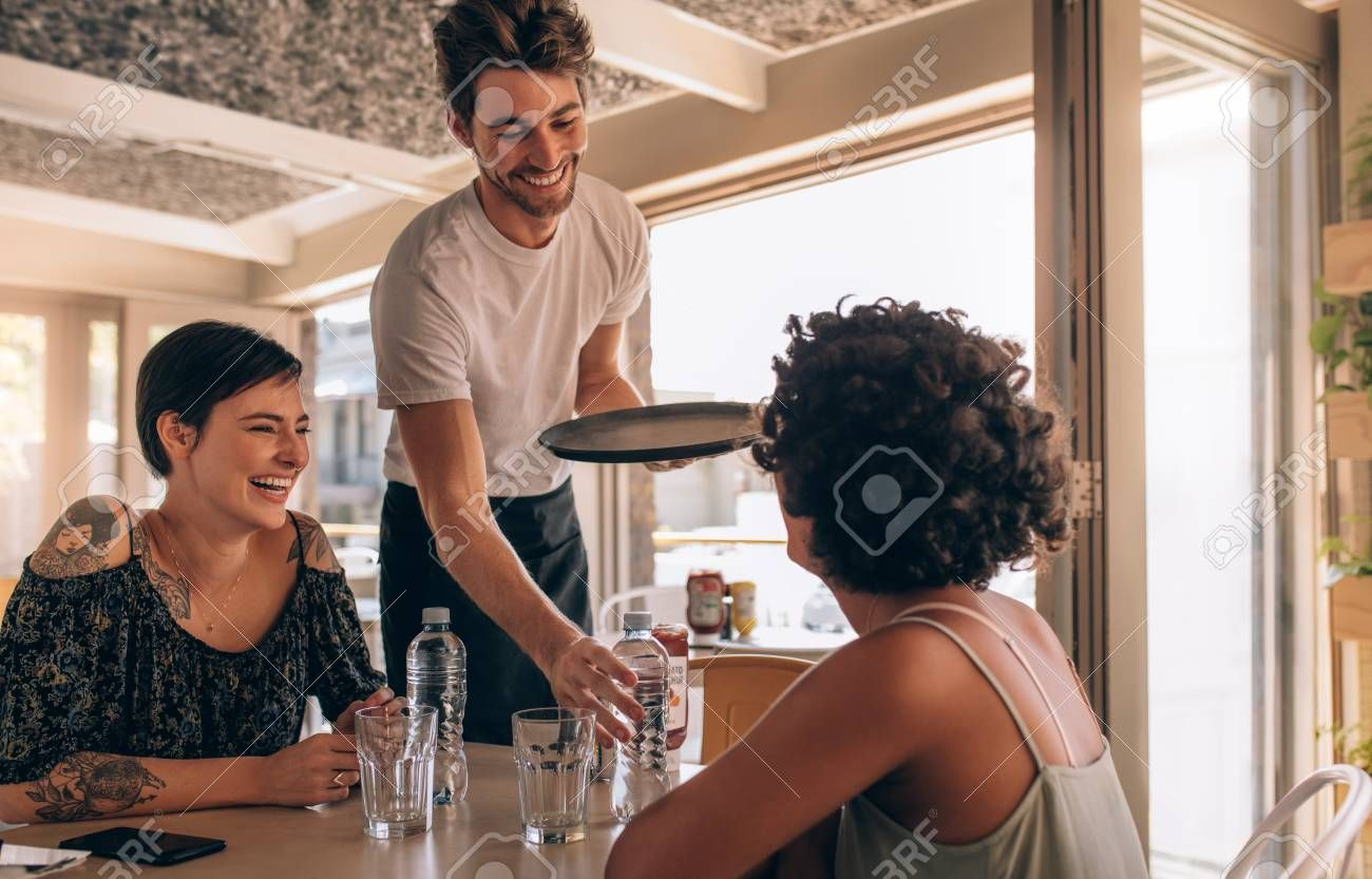 Smiling female friends at a cafe with waiter serving water. Two young women sitting at a restaurant. , #sponsored, #cafe, #waiter, #friends, #Smiling, #female