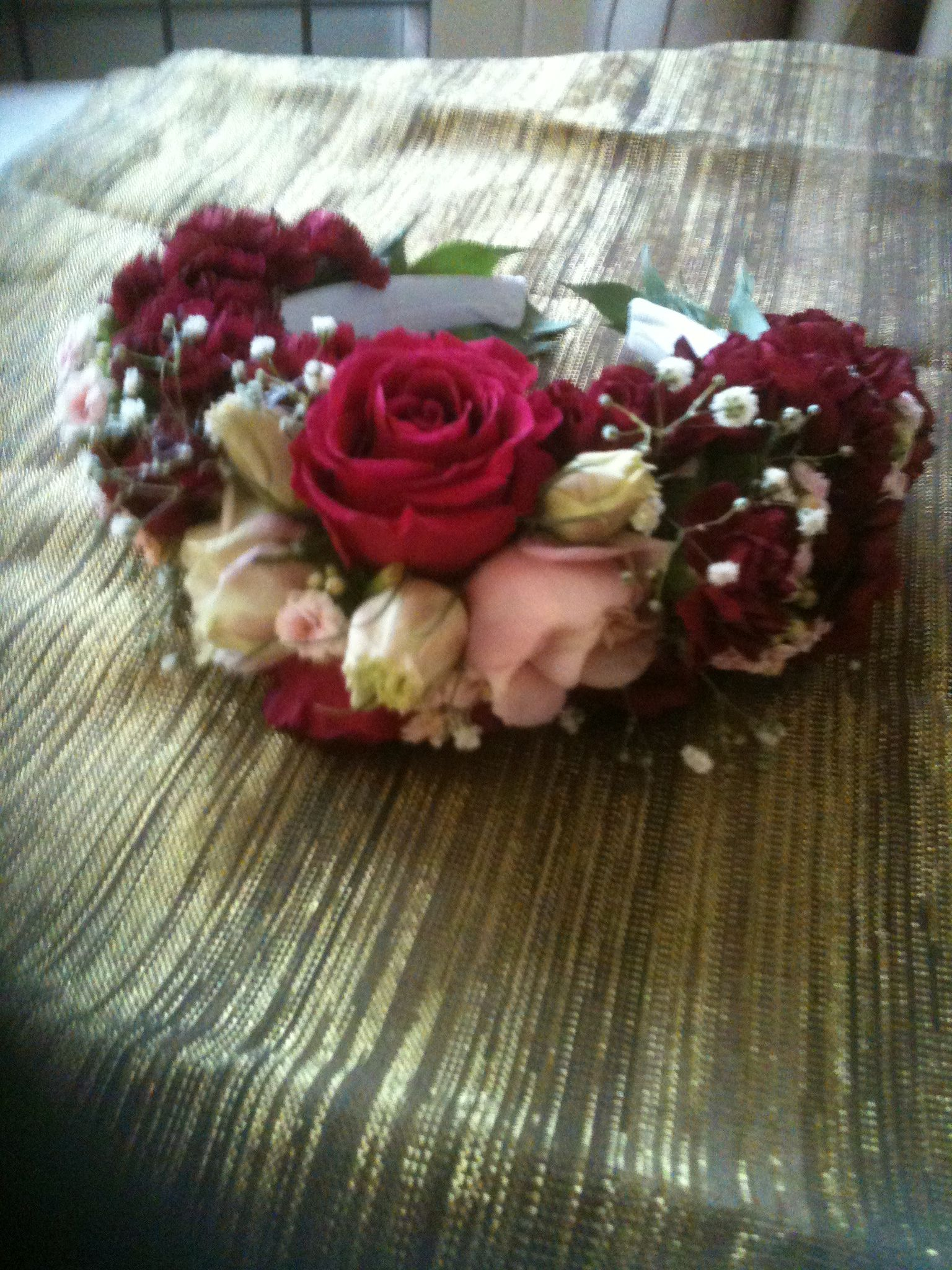 A floral headress using fresh flowers, roses gypsophila, carnations in deep pinks and pale pinks.