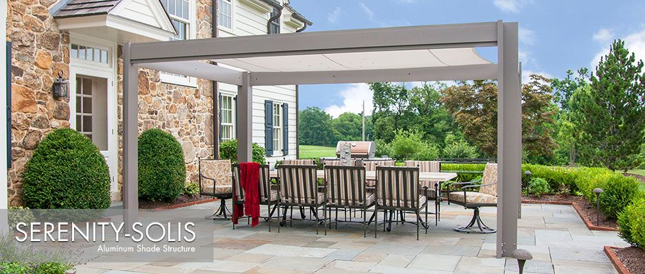 Aluminum shade structure with fabric canopy over stone patio next to traditional stone house & Aluminum shade structure with fabric canopy over stone patio next ...