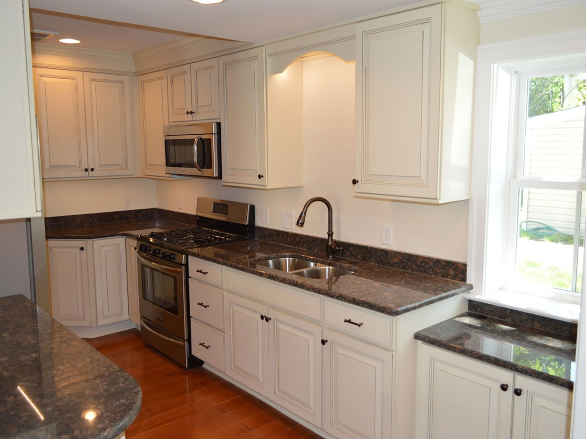 Picture Of Woman And Large Spotted Dog In Kitchen Woman Working At Double Wide Center Island Built Of Gray Cabin Kitchen Design Kitchen Cabinet Design Kitchen