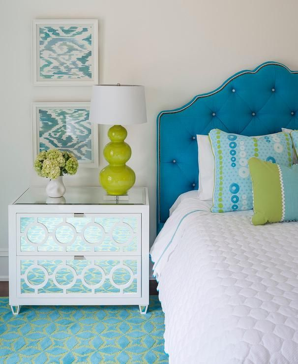 Contemporary blue and green girl's bedroom boasts a Worlds Away White Lacquer and Mirror 2 Drawer Nightstand placed on a blue and green area rug and topped with a Robert Abbey Triple Gourd Lucite Table Lamp positioned in front of two stacked blue ikat prints mounted on a wall beside a blue velvet tufted bed dressed in a white scalloped blanket topped with blue and green pillows.