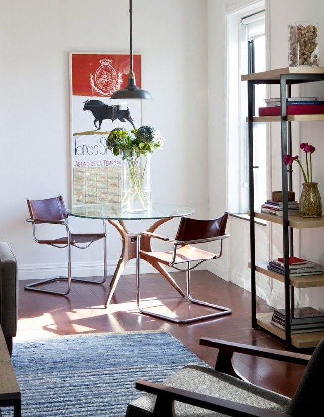 Dinning nook with a glass table, modern leather chairs, and a black pendant light