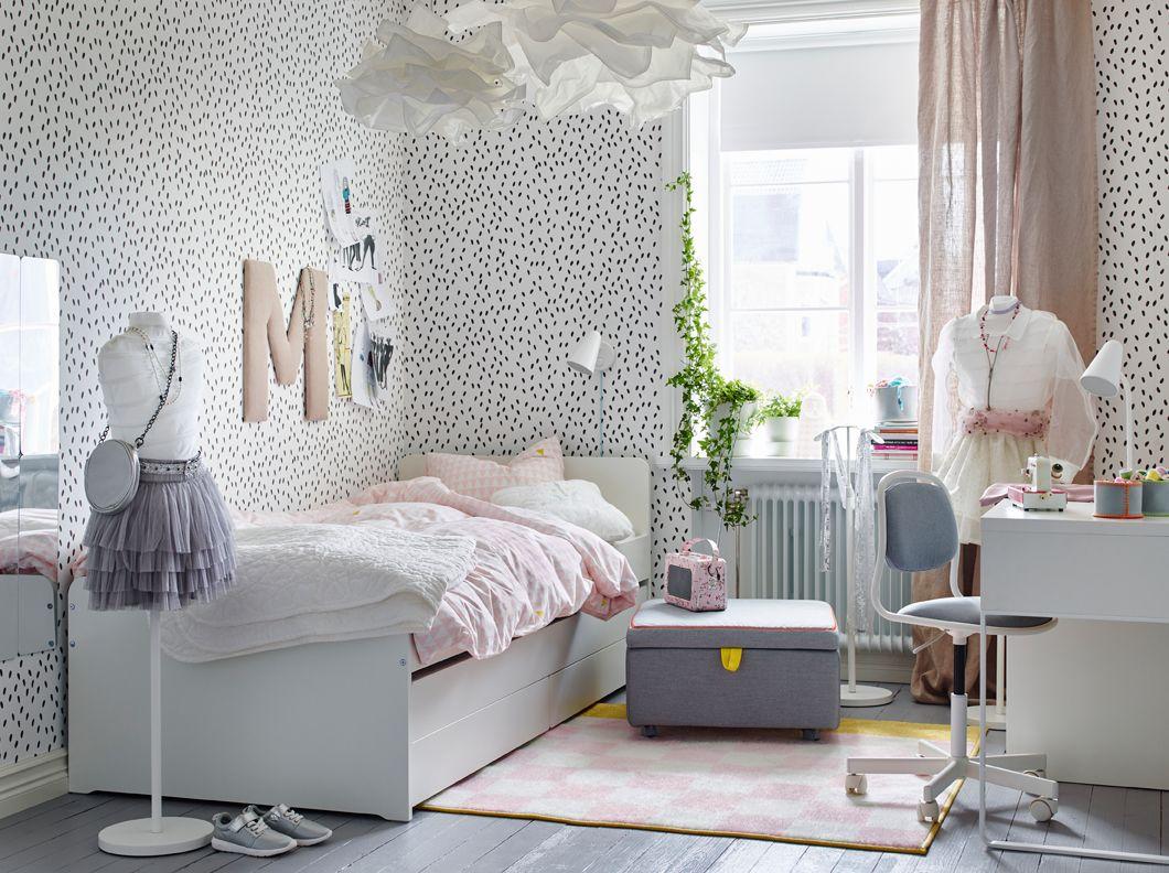 Cameretta con pareti bianche punteggiate di nero e letto bianco con ...