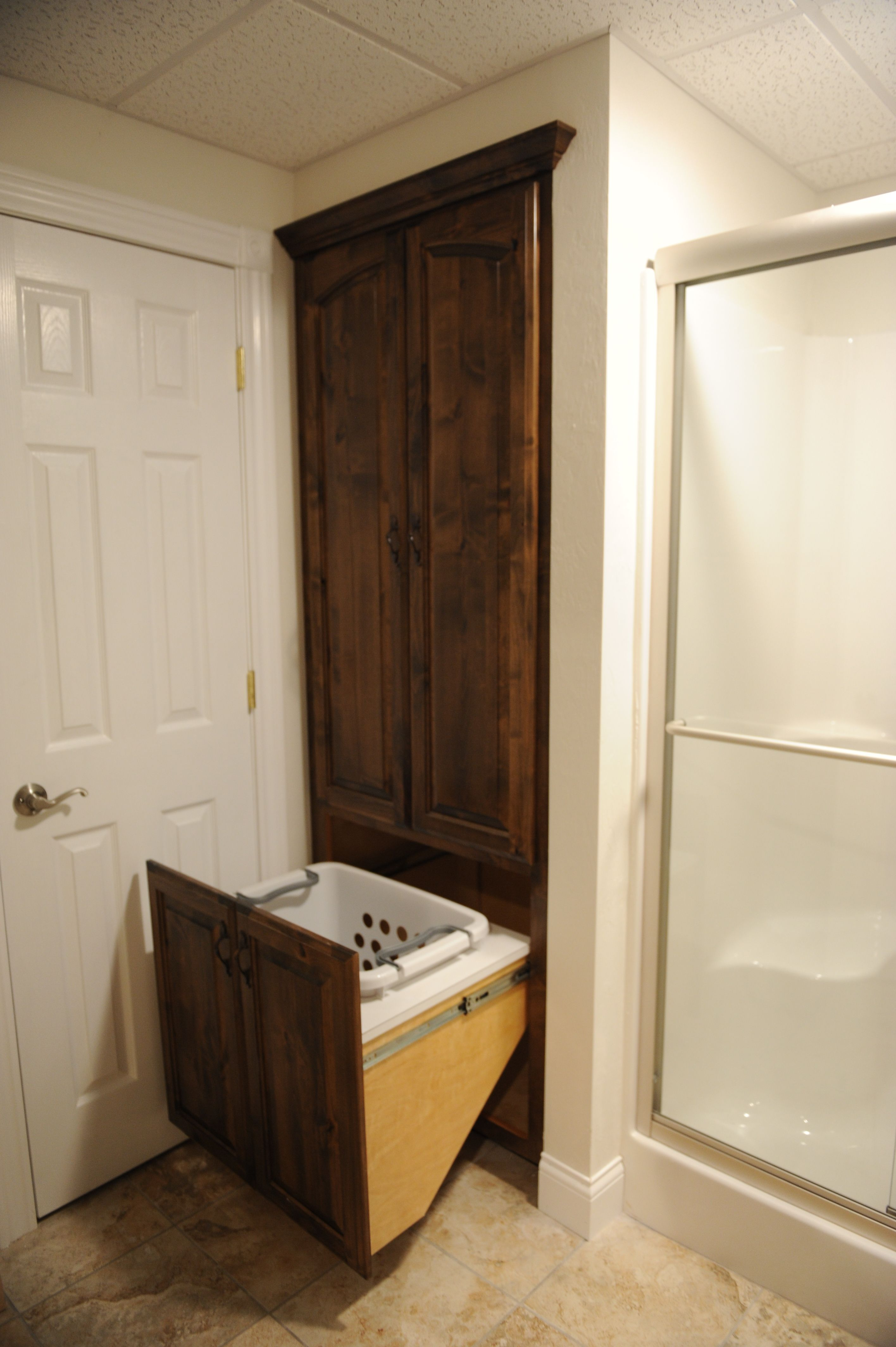 Roll out hamper storage in the bath room. lustigcabinets.com ...