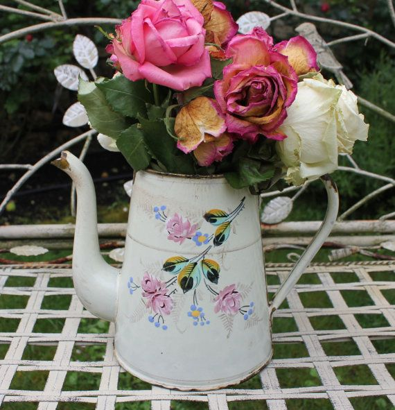 This white vintage French enamel coffee pot with hand painted roses and an ill fitting lid is just precious. It is banged up a bit and in less