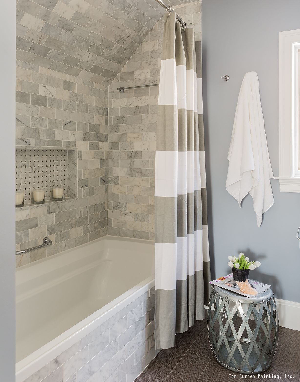 a gorgeous bathroom remodel with a tile shower, white trim and a