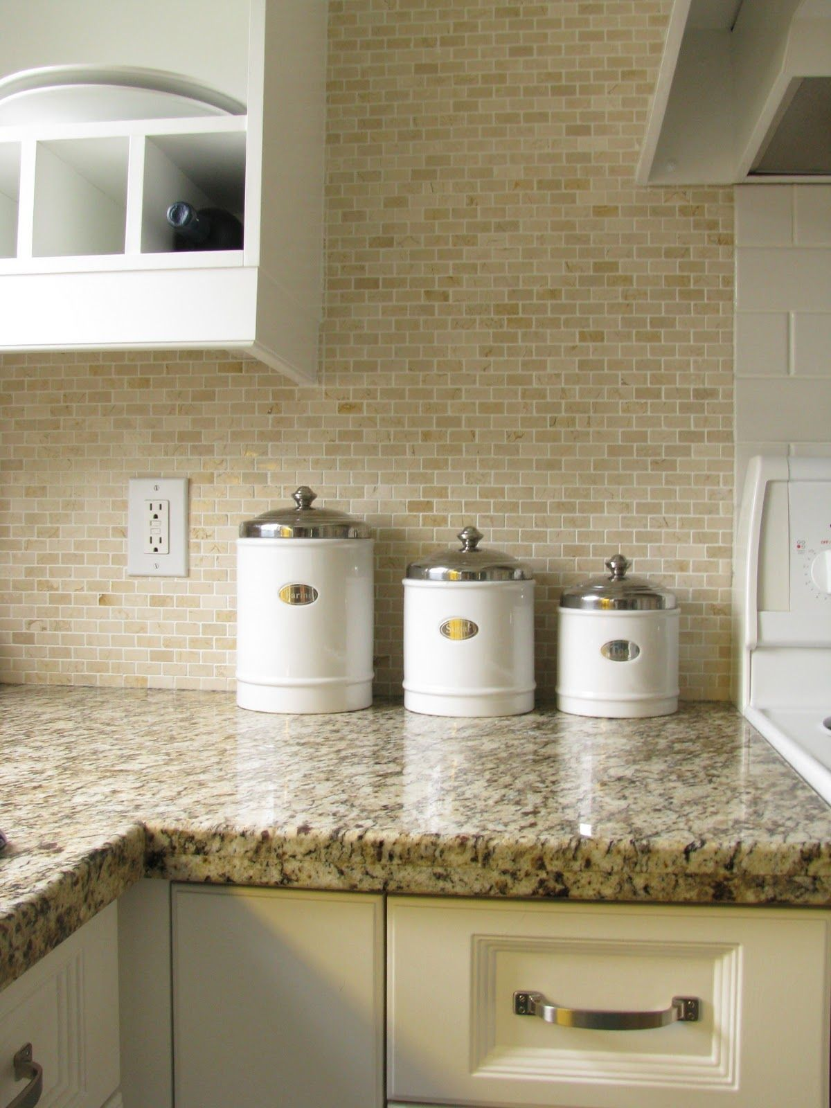 The backsplash is Crema Marfil marble It gives such a French look to the kitchen with the fresh white cabinets Observe the backsplash large subway