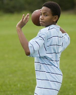 Boy playing football - Daniel H. Bailey/Photolibrary/Getty Images