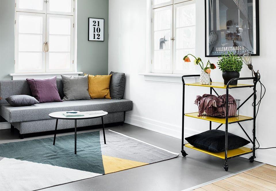 Stue med sofa-hjørne med gråt linoleumsgulv, grå sofa, farverige ...