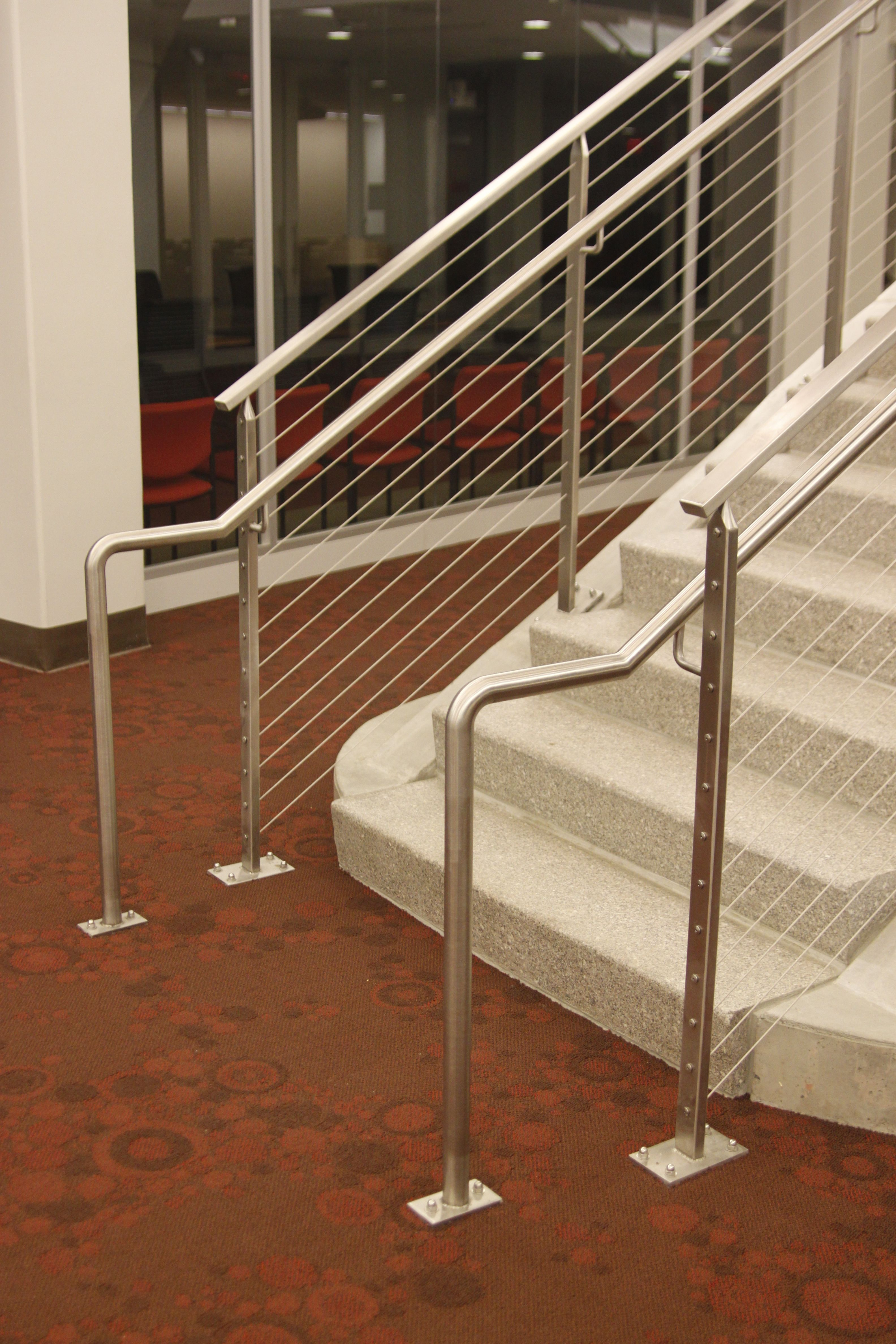 Stair railings made with rectangular stainless steel tubing posts and  stainless steel cables. These stair