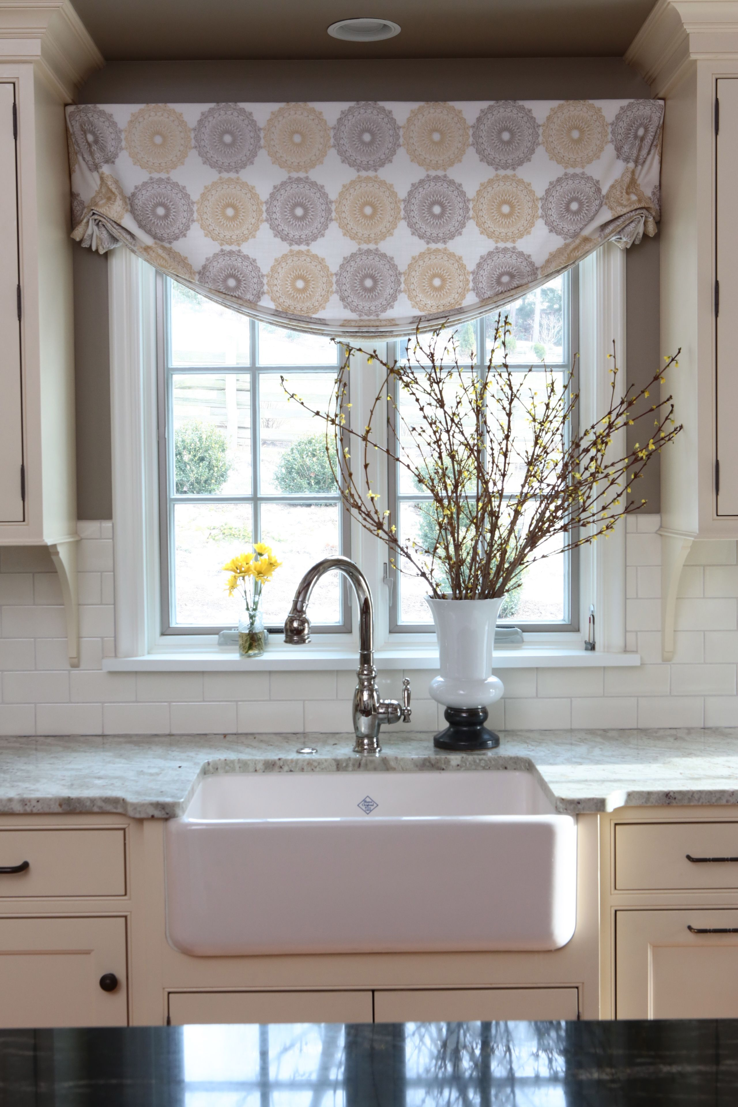 Window under kitchen cabinets  sunny yellow kitchen cabinets  farmhouse sink  relaxed valance