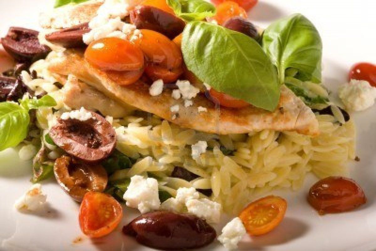 Gourmet healthy dinner of chicken on a bed of rice, with feta cheese, cherry tomatoes, kalamata olives and fresh basil. Stock Photo - 807918...