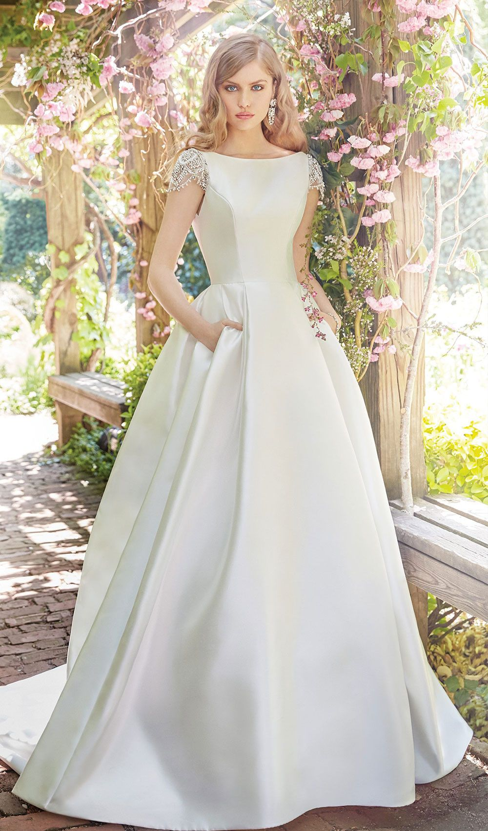 Try this white mikado modest wedding dress with jeweled cap sleeves