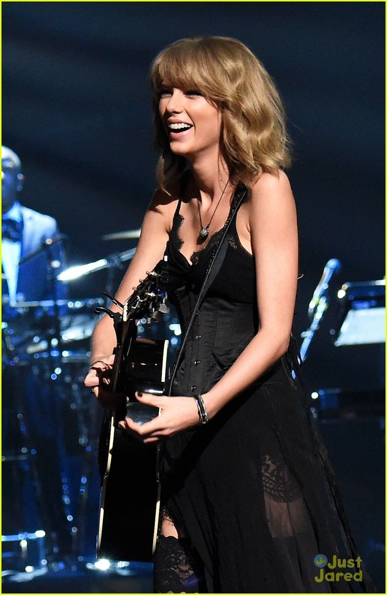 Taylor Swift plays the guitar to accompany Madonna during a surprise appearance on stage at the 2015 iHeartRadio Music Awards